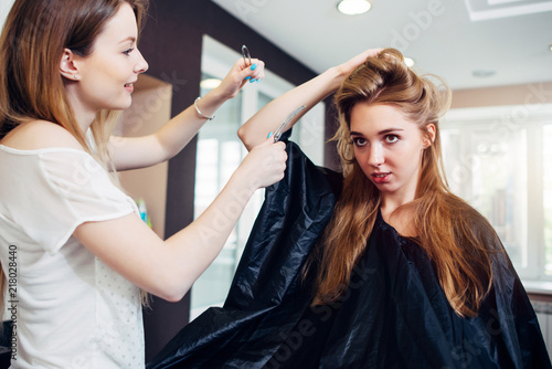 Foto Spatwand Kapsalon Smiling female hairdresser doing coiffure to pretty young woman with long fair hair in hairdressing salon