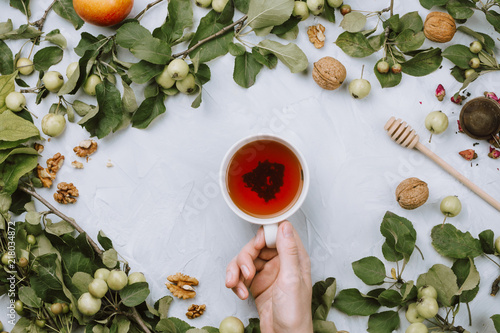 Foto Murales Warm autumn flatlay with apple branches, fruits, walnuts, red tea in a cup and woman's hand on grey cement background