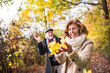 Leinwanddruck Bild - Senior couple on a walk in a forest in an autumn nature, holding leaves.