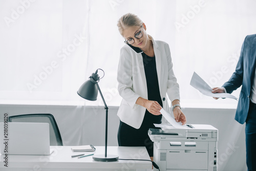 Fridge magnet businesswoman talking on smartphone while using printer in office with colleague near by