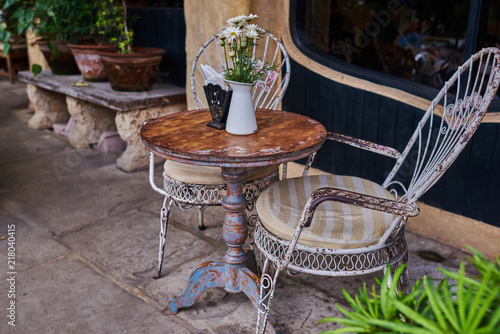 Old White Antique Wrought Iron Furniture, Shabby Chic Exterior. Set Of  Round Table With Flowers And Two Elegant Chairs In The Street In The Old  Town.