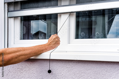 Screen on window. hand holds anti-insect mosquito net on pvc window - 218042681