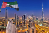 Arabian man watching night cityscape of Dubai with modern futuristic architecture in United Arab Emirates - 218043613