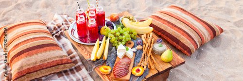 Picnic on the beach at sunset in the style of boho. Concept outdoors evening healthy dinnner with fruit and juice - 218046416