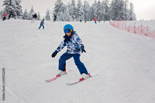 Leinwanddruck Bild Cute preschool child, skiing in Austrian winter resort on a clear day