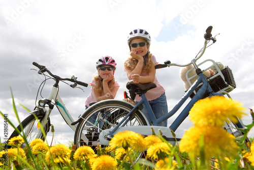 Foto obraz na płótnie canvas jednoczęściowy - Twin sisters relax from riding their bicycles in front of a dandelion field.  They have happy smiling faces on them as they enjoy the outdoor  cycle tour.