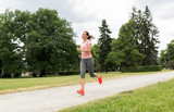 fitness, sport and healthy lifestyle concept - smiling woman with earphones running at park and listening to music