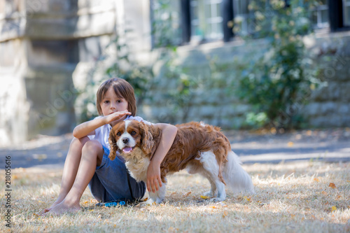 Foto Murales Beaugtiful preschool children, playing with sweet dog in the park