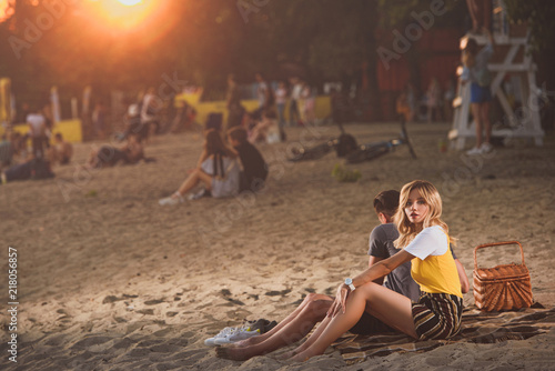 Foto Murales young couple sitting on blanket with straw basket on river beach in evening
