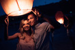 young couple launching sky lantern on river beach in evening