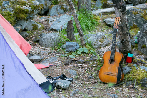 Foto Murales Tourist tent and musical guitar by the tree. Tourist camp in the forest.