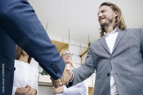 Foto Murales Businessmen handshaking after deal agreement