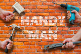 hands holding tools on brickwall background with handyman writing on it