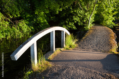 Fototapeta Small bridge at lakeside park summer sunset