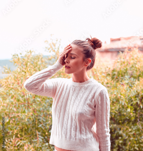 Foto Murales Pretty beautiful young woman with headache, in white sweater and underwear, standing on balcony. Tuscany, Italy. Small depth of field.