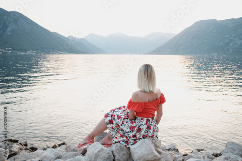 Foto Murales Back view of blonde woman in red T-shirts looking at the sea at sunset in Montenegro