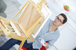 man painting on a canva at home