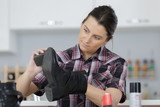 young woman cleaning shoes in her kitchen - 218098637