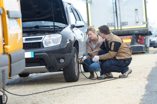 mechanic fixing a car problem on the road