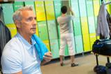 senior man sitting in the locker room in the gym - 218101074