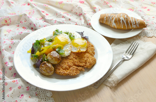 Breakfast with eggs, potatoes, schnitzel and croissant - 218103883