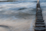 Wooden breakwater shot with long exposure at dusk