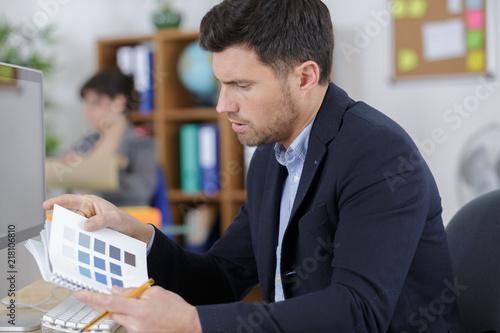 człowiek w biurze patrząc na broszury próbek kolorów