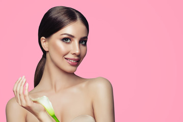 Young spa woman with healthy skin and white flowers on pink background. Facial treatment, cosmetology and spa treatment