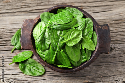 Foto Murales Spinach leaves on wooden background