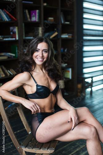 Uśmiechnięta kobieta w czarnym obsiadaniu na krześle