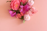 Directly above view of pink and purple camellias and azaleas on pink background with copy space (selective focus)