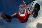 Low Angle View of Man Hanging on Basketball Hoop - 218137420
