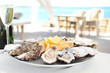 Leinwanddruck Bild - Fresh oysters with cut juicy lemon served on table