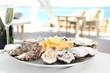 Leinwanddruck Bild - Fresh oysters with cut juicy lemon served on table