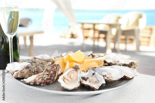 Leinwanddruck Bild Fresh oysters with cut juicy lemon served on table