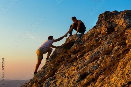 Leinwanddruck Bild Man Rock Climbing with another Man Helping