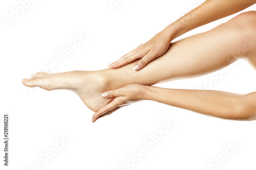 Leinwanddruck Bild closeup of female hands applying hand cream on leg on white background