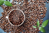 Coffee beans background with white cup in the middle and green leaves