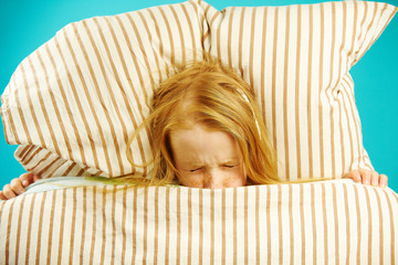 Girl in bed with fear closed her eyes, concerned, sees nightmares, afraid to get out from under blanket, top view.
