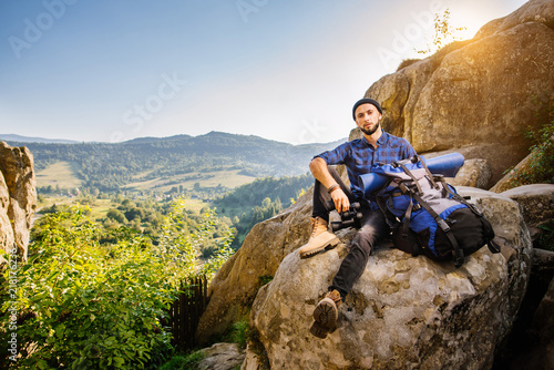 Foto Murales Tired man traveler sitting on the rocks and holding a backpack