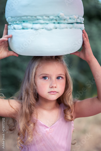 Cute little girl holds French Macaron on her head