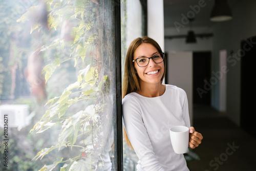 Piękna młoda kobieta opiera na okno, trzyma kubek.