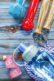 Measuring tape skipping rope dumbbells water shaker on wooden bo - 218242668