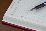 Concepto de negocio con agenda de papel y pluma