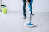 Husband housekeeping and cleaning concept, Happy young man in blue rubber gloves wiping dust using mop while cleaning on floor at home - 218257025
