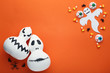 Halloween candy corns with ghost and pumpkins on orange background