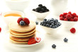 Tasty pancakes with berries on white wooden table
