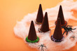 Chocolate halloween hats with spiders on orange background