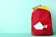 Red backpack with school supplies on mint background