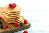 Tasty pancakes with raspberries on wooden table